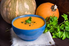 Pumpkin vegetarian soup in a blue bowl served with parsley, olive oil and pumpkin seeds on a dark wooden background royalty free stock images