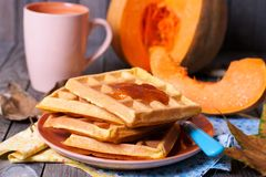 Pumpkin waffles. In a plate on a wooden table Stock Images