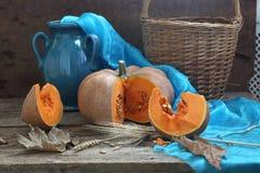 Pumpkin, wattled basket and dark blue jug Stock Image
