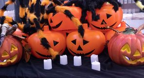 Pumpkin and white candles on black fabric in Halloween. stock image
