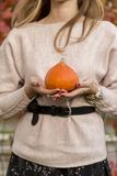 Pumpkin in woman hand out door royalty free stock image