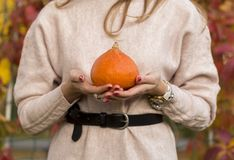 Pumpkin in woman hand out door royalty free stock photo