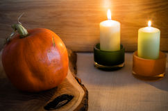 Pumpkin on wooden board and candles Stock Images