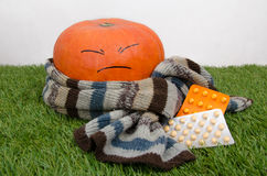 Pumpkin wrapped in a scarf and drugs. Sick pumpkin wrapped in a warm scarf and pills and vitamins royalty free stock image