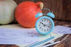 Pumpkings, bosquejos del lápiz y despertador en la tabla de madera marrón Preparación al día de fiesta de Halloween Fotos de archivo