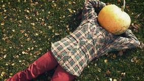 Pumpkinhead die op gazon liggen stock videobeelden