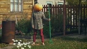 Pumpkinhead-Person mit Rührstange im Garten stock video footage
