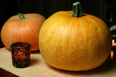 Pumpkins. And candle in stained glass on bamboo mat Royalty Free Stock Image