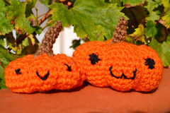 Pumpkins amigurumi crochet toy. Crocheted pumpkins with vine leafs on the background. Doll toys amigurumi style Stock Image
