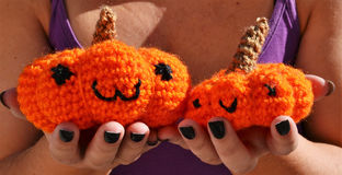 Pumpkins amigurumi crochet toys. Crocheted pumpkins gift with hands offering them. Doll toys amigurumi style Stock Photography