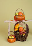 Pumpkins and Apples in Baskets on Wood Bench Royalty Free Stock Photography