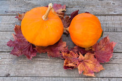 Pumpkins with autumn colorful leaves on wooden table Royalty Free Stock Images