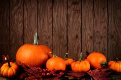 Pumpkins and autumn leaves against rustic wood Stock Photography