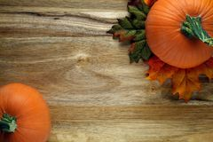Pumpkins and autumn leaves. On wooden background Royalty Free Stock Photography
