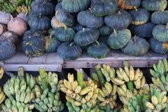 Pumpkins and bananas. In market Royalty Free Stock Image