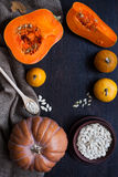 Pumpkins and a bowl with toasted pumpkin seeds, wooden spoon royalty free stock images