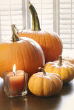 Pumpkins with candle on table Stock Image