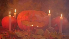 Pumpkins and candles in the smoke. Halloween concept stock video