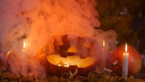 Pumpkins and candles in the smoke. Halloween concept stock video footage