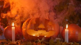 Pumpkins and candles in the smoke. Halloween concept stock footage