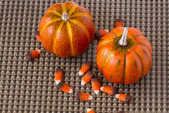 Pumpkins and Candy corn decorations on a brown woven background. Two orange pumpkins and festive candy corn on a brown woven background royalty free stock photography