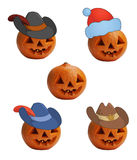 Pumpkins in caps. Set isolated on white pumpkins to halloween in different caps: the cowboy, the sheriff, the Santa Claus and the robber Royalty Free Stock Photos