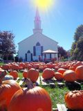 Pumpkins in church yard. Backlit pumpkins on sale in front of a church stock photos