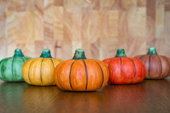 Pumpkins. Colourful ceramic little pumpkins lined up on a wooden table with light brown wooden board in a background royalty free stock image