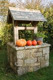 Pumpkins on the coping of a well Stock Photos