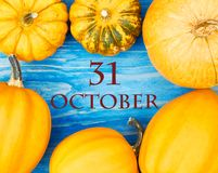 Pumpkins frame on wooden sea blue background, flat lay. Halloween and thanksgiving concept. Pumpkins create a frame around writing - 31 october, copy space for stock photography