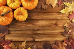 Pumpkins with fall leaves over wooden background. Top view. royalty free stock image