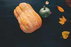 Pumpkins with fall yellow leaves on dark wooden background Stock Image