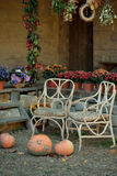 Pumpkins and flowers. At home on the porch pots of flowers, chairs and pumpkin on the ground Stock Image
