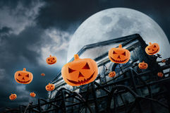 Pumpkins fly over fence and grunge building at night over cl Royalty Free Stock Images