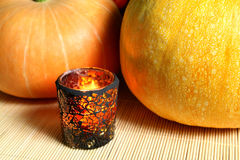Pumpkins on halloween. Pumpkins and candle in stained glass on bamboo mat. Halloween Stock Photo