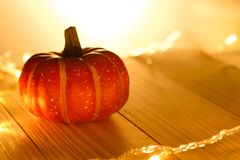 Pumpkins and lights decorate the halloween day. On the wooden floor Stock Photos