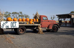 Pumpkins on Old  Farm Truck. Pumpkins on an old red farm truck with a sign advertising that the farm stand will be open in October Stock Photography