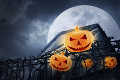 Pumpkins on old fence and grunge building at night over cloudy sky Royalty Free Stock Image