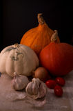 Pumpkins with onion, garlic and tomatoes. Three different pumpkins with garlic, onion and tomatoes on wooden table Stock Photo