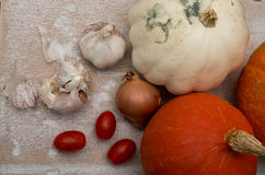 Pumpkins with onion, garlic and tomatoes. Vegetables placed on wooden table Royalty Free Stock Image