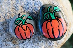 Pumpkins painted on two small rocks stock photos