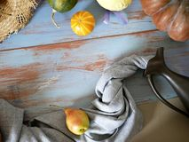 Pumpkins, pears, apples, gray fabric on a light wooden table, concept of cooking for a seasonal home holiday. Harvest, autumn, top view stock image