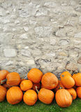 Pumpkins piled against a rustic stone wall Stock Photo