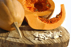 Pumpkins and Pumpkins seeds on wood and white background Royalty Free Stock Photo