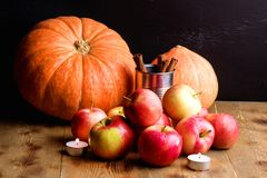 Pumpkins Red apples and Candles on wooden background Autumn harvest Cinnamon Horizontal Royalty Free Stock Photography