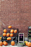Pumpkins For Sale. Against a brick wall Stock Image