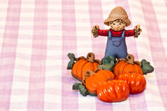 Pumpkins and scarecrow. Over a purple tablecloth vector illustration