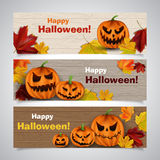Pumpkins. Set of vector Halloween headers with leaves and scary pumpkins on wooden background Stock Image