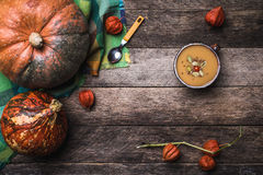 Pumpkins and soup with seeds and ground cherry on wooden table Stock Photography