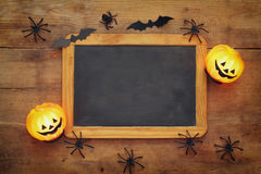 Pumpkins, spiders, bats and blackboard on wooden old table Royalty Free Stock Photos